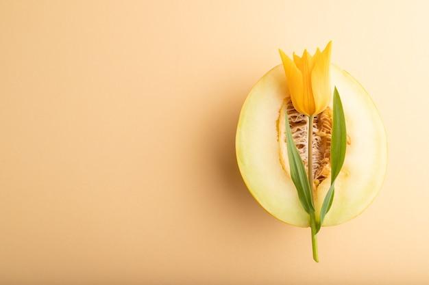 Melon jaune tranché et fleur de tulipe sur fond pastel orange. vue de dessus, mise à plat, espace de copie.