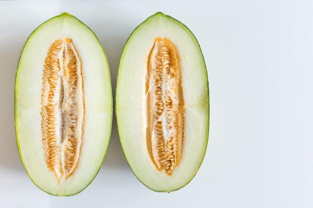 Melon de miellat fraîchement coupé sur fond blanc