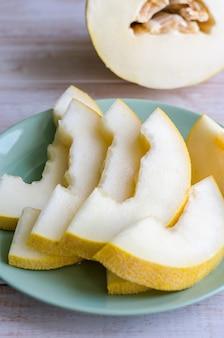 Melon mûr juteux en tranches sur une plaque.