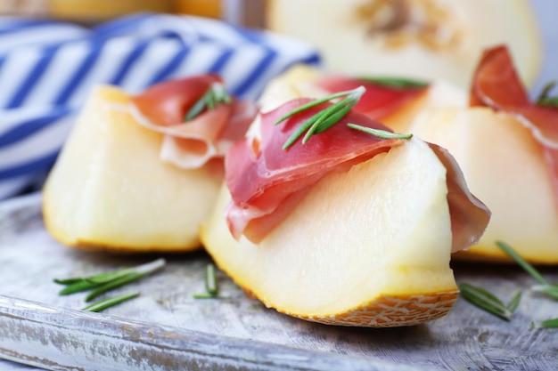 Melon avec prosciutto de jambon de parme sur table en bois, gros plan