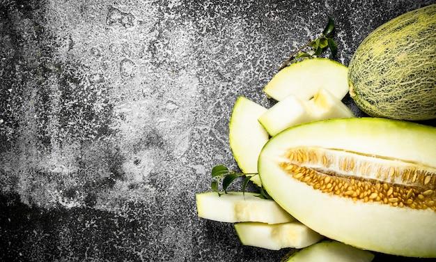Melon en tranches mûres fraîches sur table rustique.