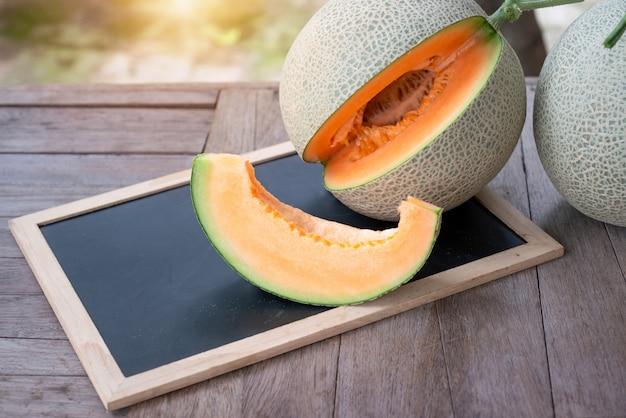 Melon vert frais coupé sur la mise au point sélective de tables en bois