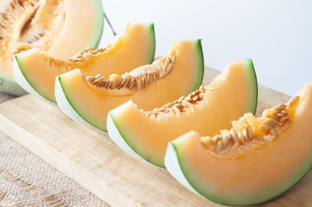 Melons frais tranchés sur une planche à découper en bois. fruits sains. mise au point sélective