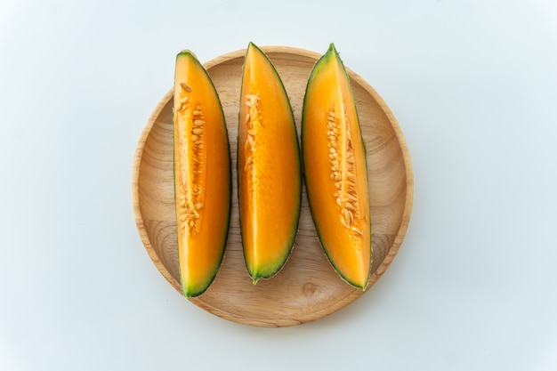 Melons frais tranchés sur une plaque en bois sur fond de tableau blanc