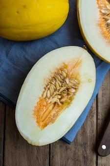Melons jaunes organiques mûrs, coupés en deux et entiers sur bois de planches sombres