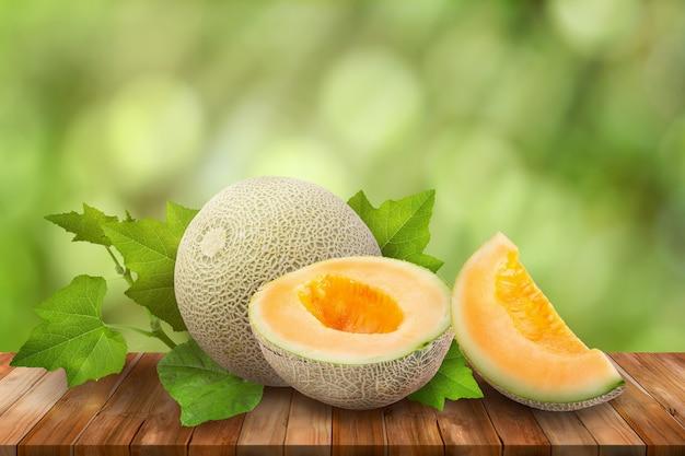 Melons de miellat sur table en bois sur vert