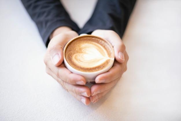 Mem main tenant une tasse de café sur fond blanc