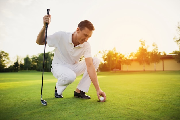 Un membre du club de golf joue sur un parcours au coucher du soleil.