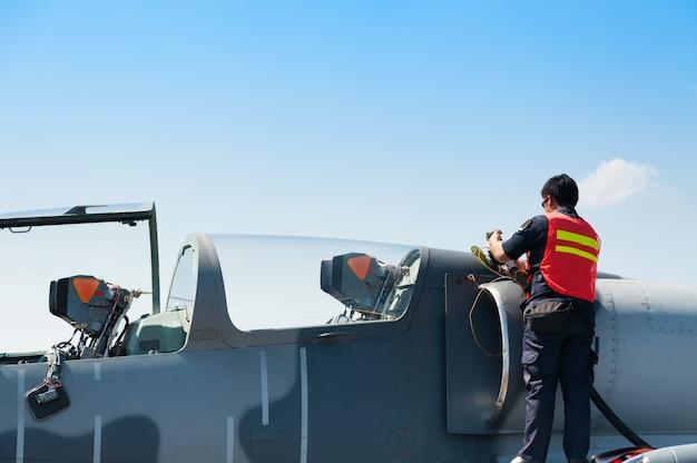 Un membre du personnel de l'armée de l'air fait le plein d'essence jusqu'à la f16 à la force royale