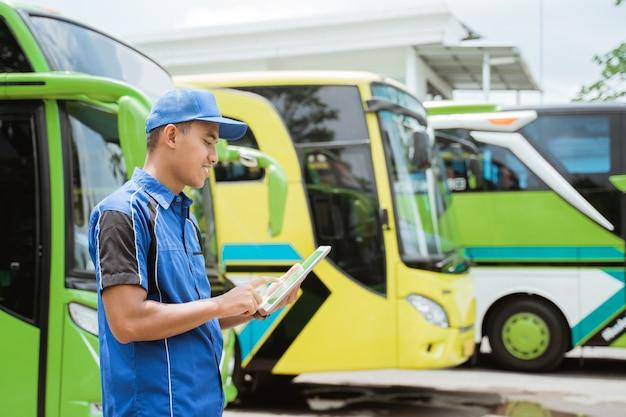 Un membre de l'équipage de bus masculin en uniforme et un chapeau sourit tout en utilisant une tablette numérique dans le contexte de la flotte de bus