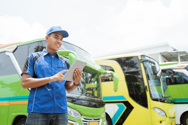 Un membre de l'équipage de bus masculin en uniforme et un chapeau sourit tout en utilisant un tampon dans le contexte de la flotte de bus
