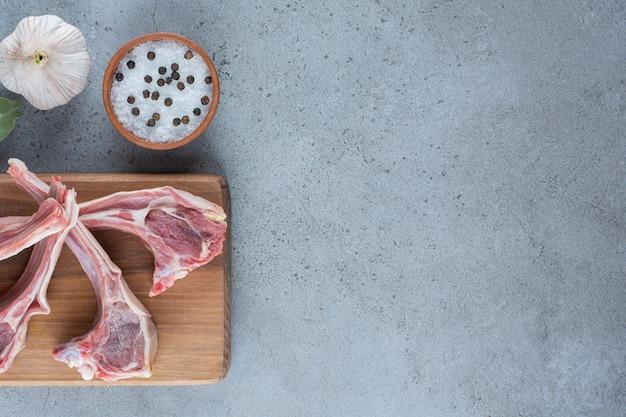 Membres d'agneau crus avec du sel et de l'ail sur planche de bois.