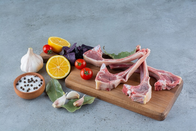 Membres d'agneau crus avec des légumes frais sur planche de bois.