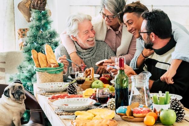 Les membres du groupe familial apprécient le déjeuner ensemble pendant la saison des jours de noël