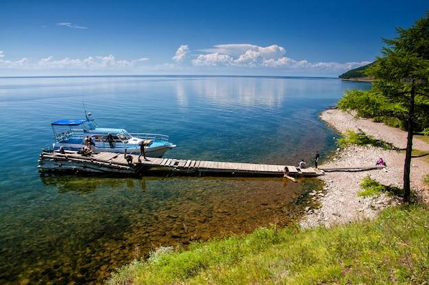 Les membres de l'équipe attendent le bateau et prennent des photos près du lac baïkal,
