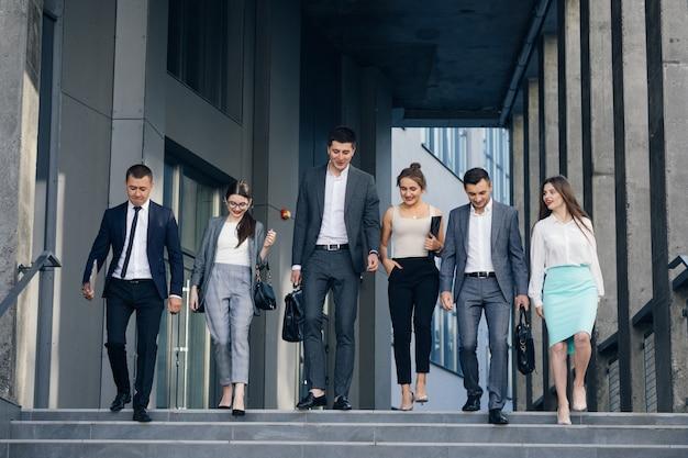 Les membres de l'équipe confiants marchent dans les escaliers. les hommes et les femmes d'affaires en costume formel vont parler sur le fond de l'immeuble de bureaux moderne.