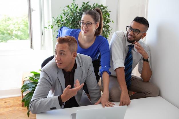 Membres de l'équipe positifs distraits de la discussion de travail