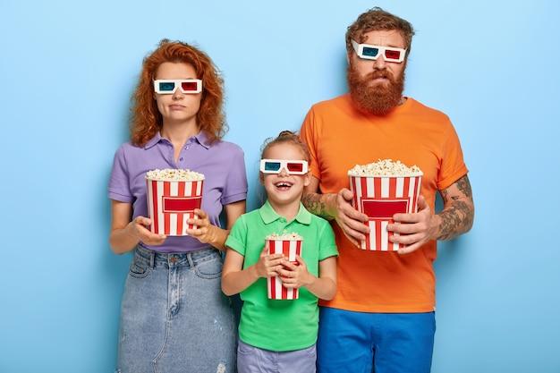 Les membres de la famille aiment regarder la télévision avec du pop-corn