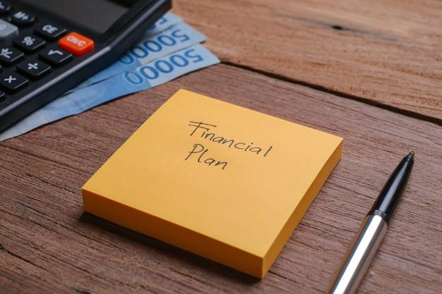 Un mémo écrit avec un plan financier avec un stylo et une calculatrice à côté sur une planche en bois
