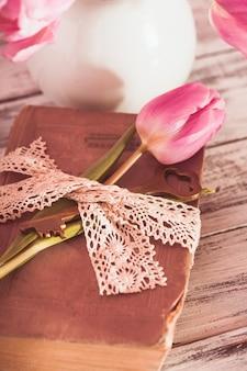 Memo nature morte avec livre, clé, dentelle vintage et tulipes roses