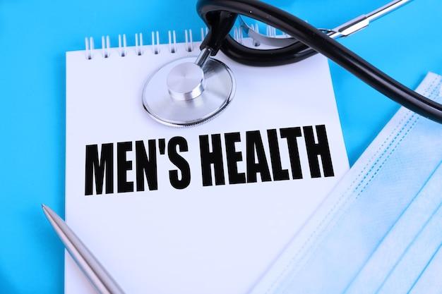 Men's health, texte écrit dans un cahier couché sur un fond bleu, avec un stéthoscope et un masque médical. concept médical.