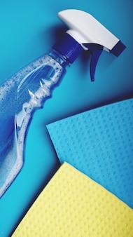 Ménage, entretien ménager et concept de ménage - chiffon de nettoyage, spray détergent sur fond bleu