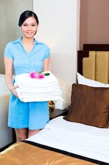 Ménage de femme de chambre dans une chambre d'hôtel asiatique