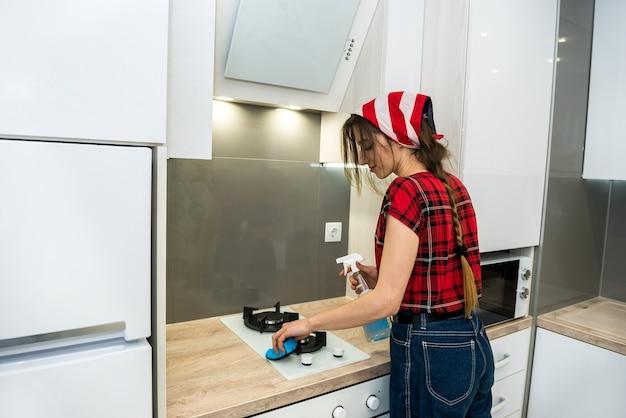 Ménagère lave la cuisinière à gaz avec un détergent dans la cuisine. nettoyage de la maison.