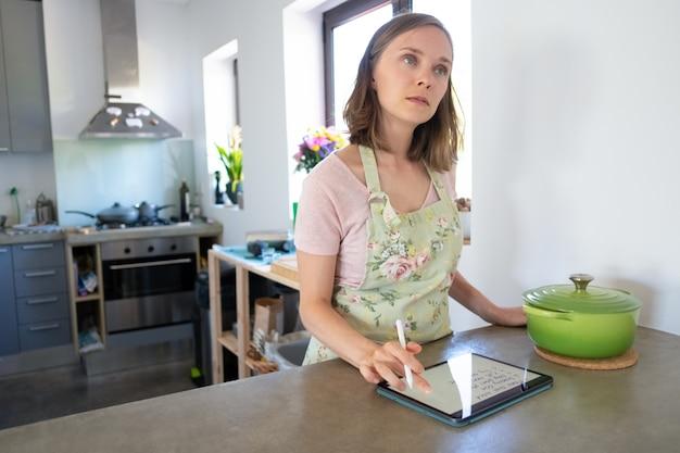 Ménagère songeuse planifiant un menu hebdomadaire et rédigeant une liste d'épicerie dans sa cuisine, en utilisant une tablette près d'une grande casserole sur le comptoir, en levant les yeux. cuisiner à la maison et concept de livre de cuisine en ligne