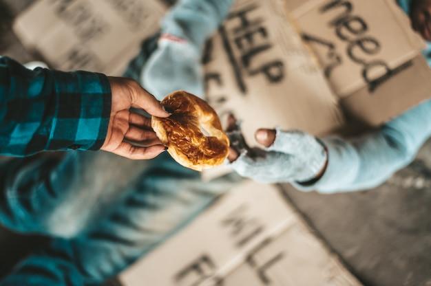 Mendiant sous le pont avec la personne qui a remis le pain.