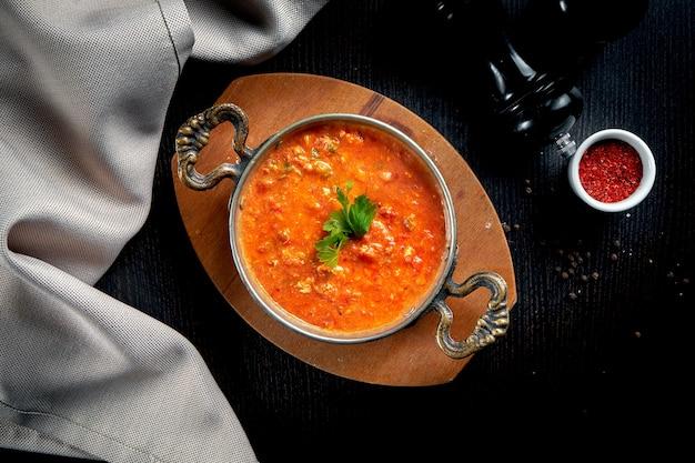 Menemen - petit-déjeuner turc populaire qui comprend des œufs, des tomates, des poivrons verts et des épices dans une casserole en cuivre sur fond noir