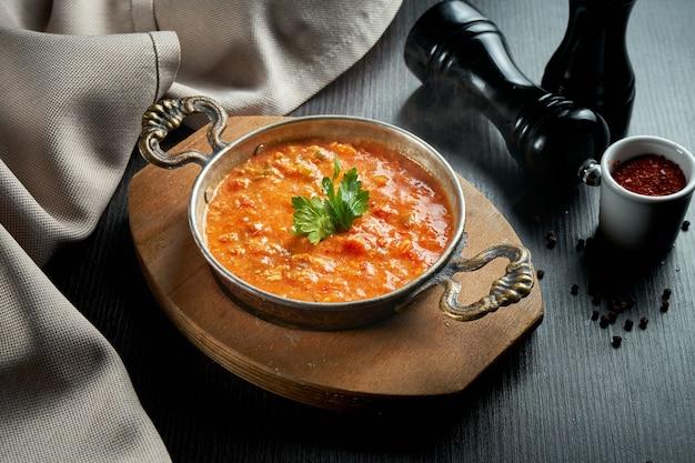 Menemen - petit-déjeuner turc populaire qui comprend des œufs, des tomates, des poivrons verts et des épices dans une casserole en cuivre sur tableau noir