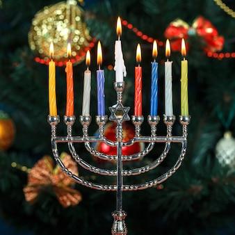 Menorah avec des bougies pour hanoukka sur le fond du nouvel an des arbres