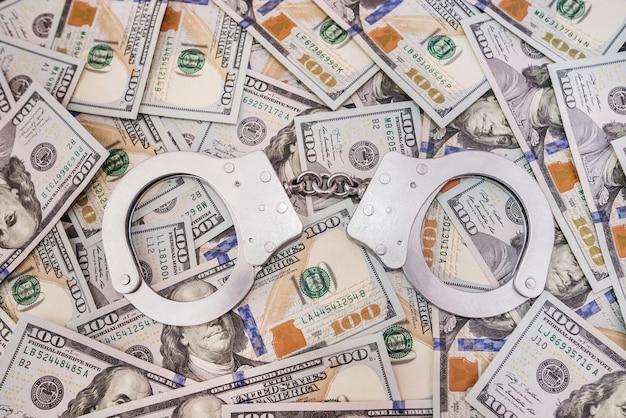 Menottes en argent et dollars américains, concept de crime.