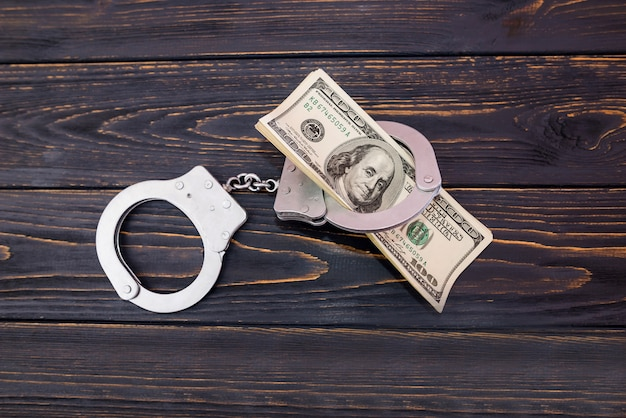 Menottes en argent et dollars américains sur fond de bois, concept de crime.