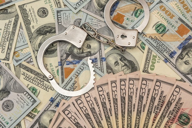 Menottes en argent se trouvant sur le dollar américain, concept de crime