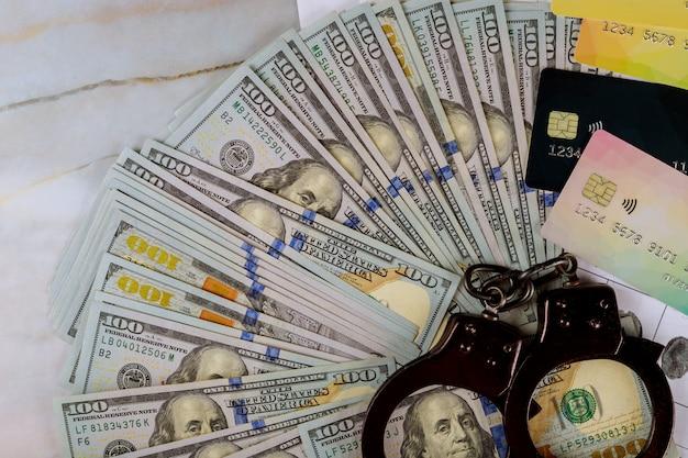 Menottes, billets de banque en dollars américains, cartes de crédit en espèces, fraude en ligne sur la cybercriminalité