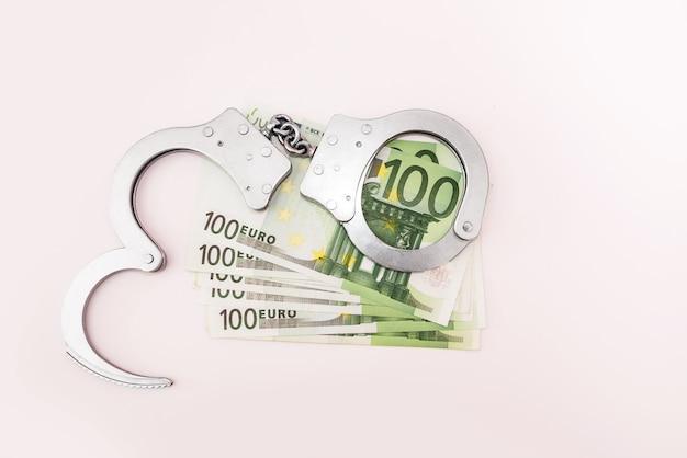 Menottes et billets en euros sur fond blanc. notion de criminalité.