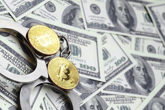 Les menottes et les bitcoins de la police reposent sur un grand nombre de dollars