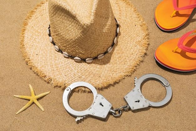 Menottes chapeau pantoufles et étoile de mer sur le concept de sable sur le thème de la punition pour vol sur la plage
