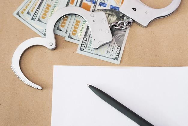 Menottes avec des dollars et une feuille de papier vierge avec un stylo