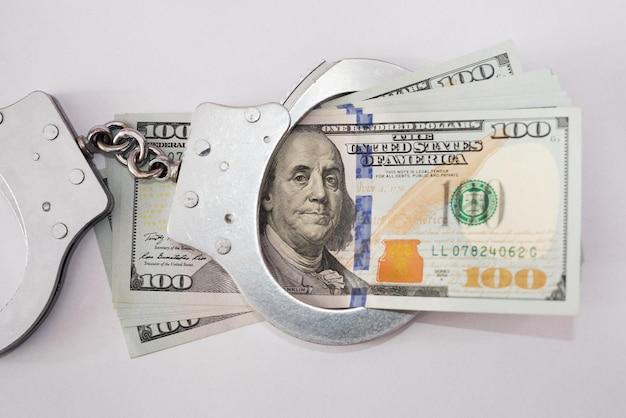 Menottes avec des dollars sur fond blanc.