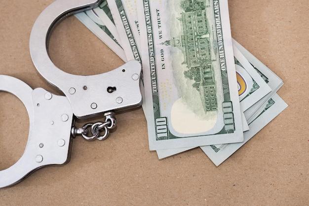 Menottes avec des dollars sur fond marron. notion de criminalité.