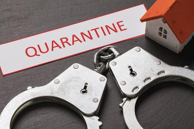 Menottes et étiquette avec texte le concept de punition pour violation de la quarantaine à domicile