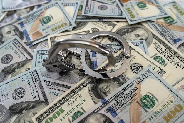 Menottes en fer sur 100 dollars américains. concept de crime