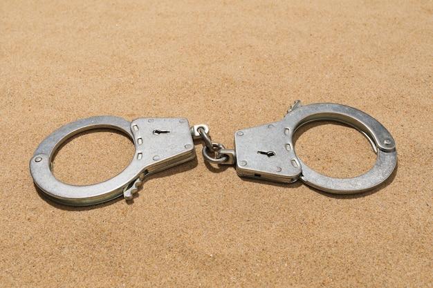 Menottes fermées sur le sable, gros plan