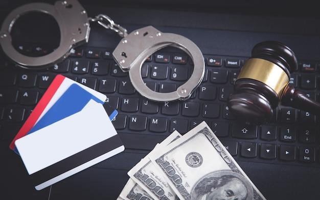 Menottes, marteau, carte de crédit, argent sur clavier d'ordinateur portable.