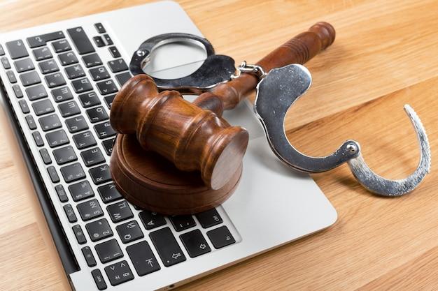 Menottes et marteau sur un ordinateur portable