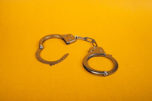 Menottes en métal sur fond jaune, concept d'arrestation.