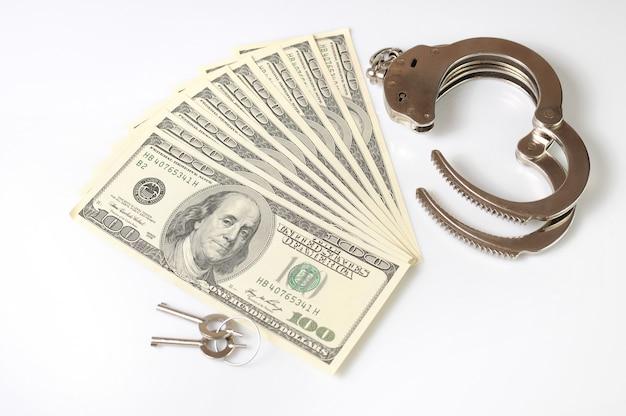 Menottes en métal ouvertes, clés et pile de dollars américains en espèces